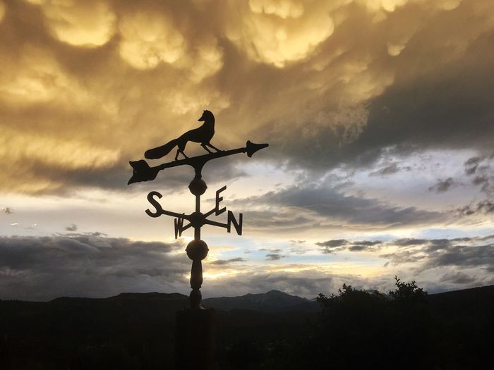 Low angle view of weather vane against cloudy sky