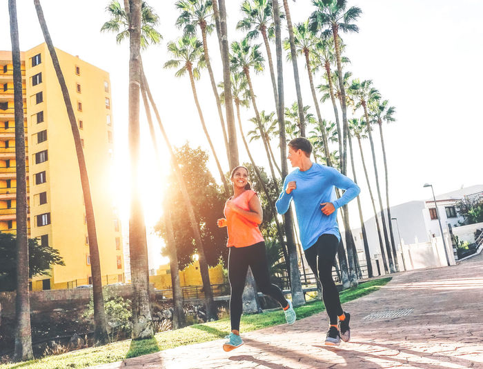 Young couple jogging on footpath in city against clear sky