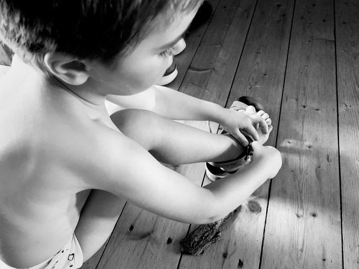 High angle view of boy sitting on wooden floor