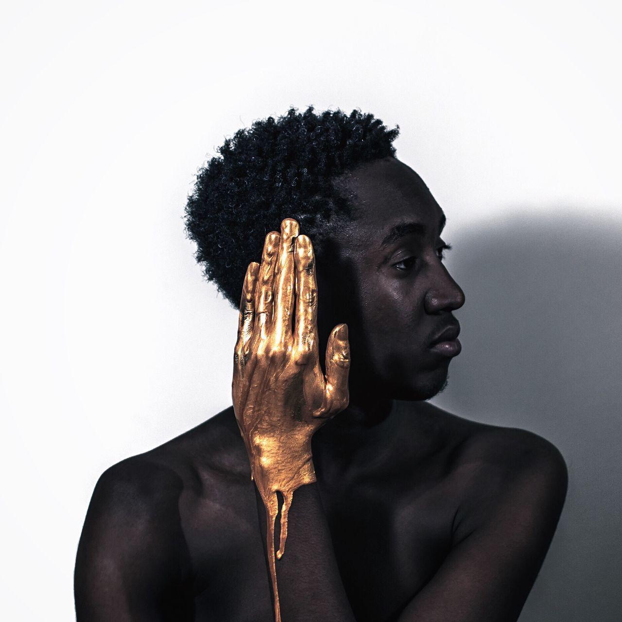 Golden paint dripping from man hand