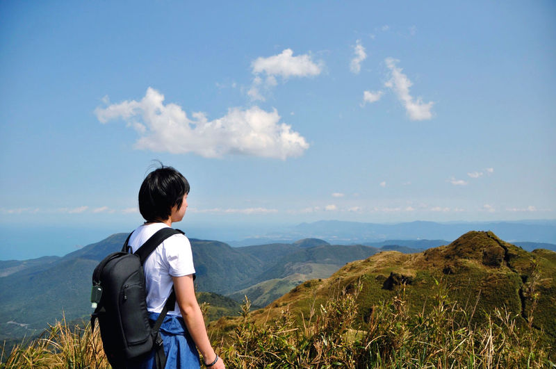 One person standing on the peak enjoy valley view. rear view of man standing on mountain against sky