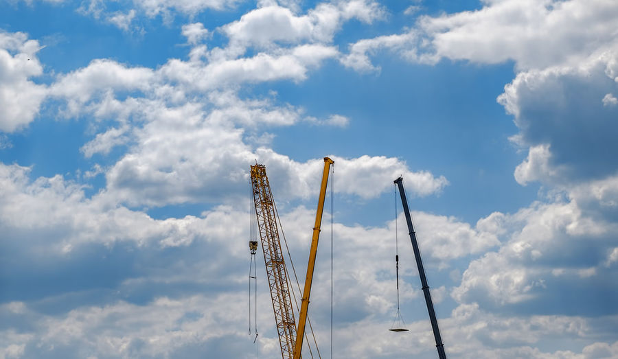 construction cranes in the blue sky with clouds Construction Cranes In The Blue Sky With Clouds Crane - Construction Machinery Cloud - Sky Sky Low Angle View No People Day Nature Industry Outdoors Construction Industry Blue Machinery Construction Site Sunlight Tall - High Metal Beauty In Nature Built Structure Development Architecture Construction Equipment Pollution