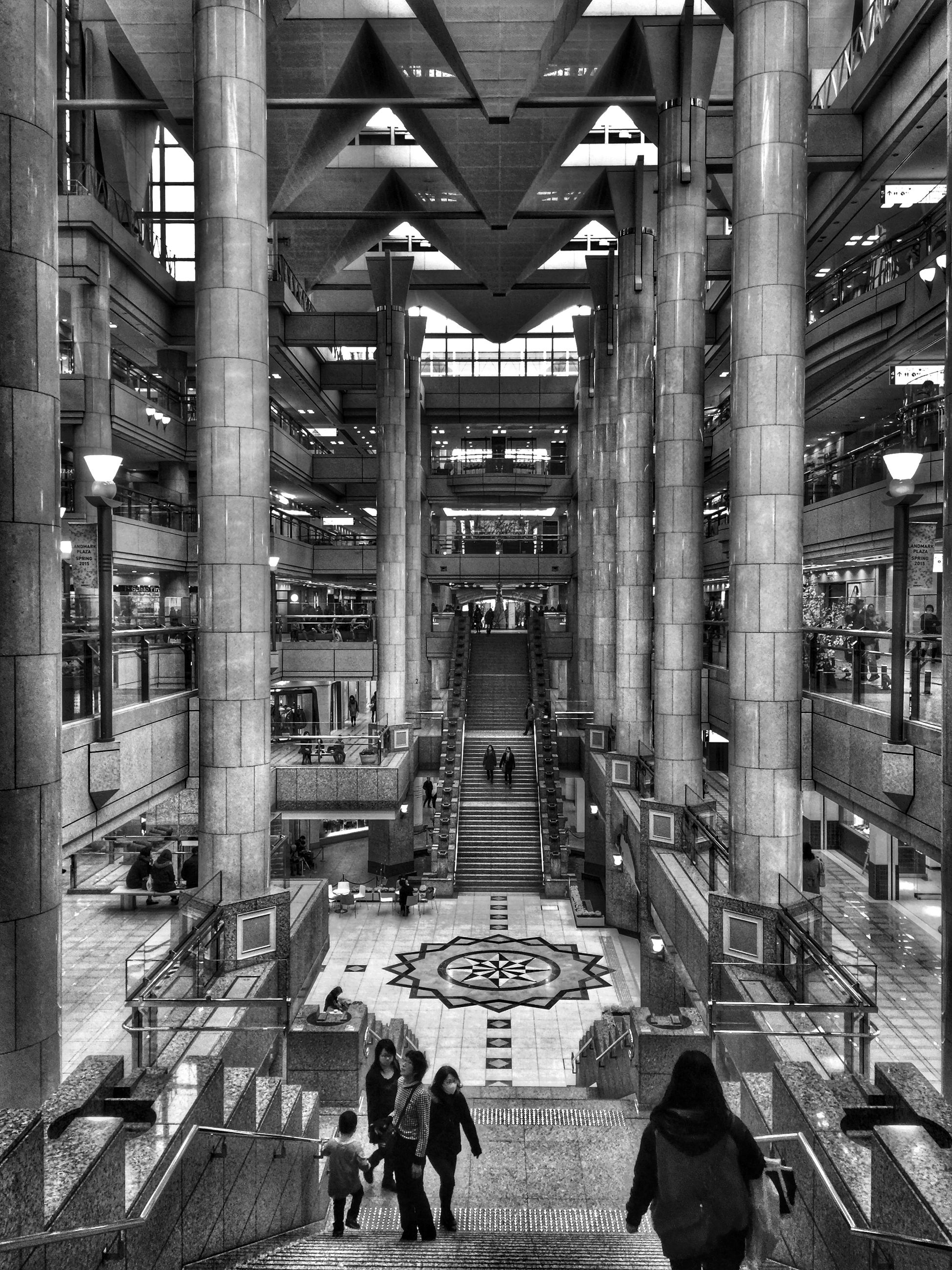 indoors, men, architecture, person, lifestyles, built structure, large group of people, leisure activity, walking, ceiling, architectural column, building, city life, standing, building exterior, group of people, shopping mall, crowd, medium group of people