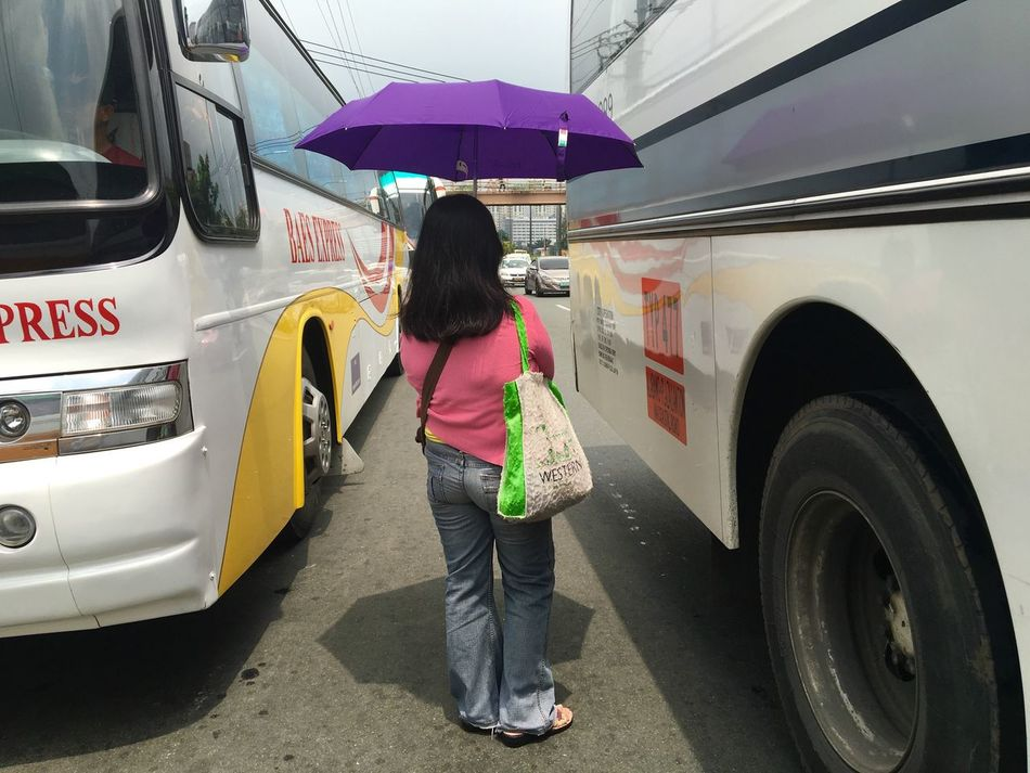 A commuter waits for a ride between buses plying along Roxas Boulevard in Paranaque, Metro Manila, Philippines. Transportation Mode Of Transport Full Length Rear View Land Vehicle Public Transportation Casual Clothing Lifestyles Road City Life Bus Philippines Roxas Boulevard Umbrella People And Places