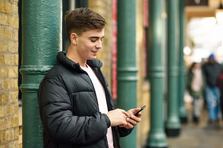 Young urban man using smartphone in urban background in London, UK Technology Wireless Technology Young Men Communication Young Adult One Person Mobile Phone Focus On Foreground Connection Smart Phone Text Messaging Portable Information Device Looking Incidental People Standing Telephone Real People Using Phone Outdoors Warm Clothing