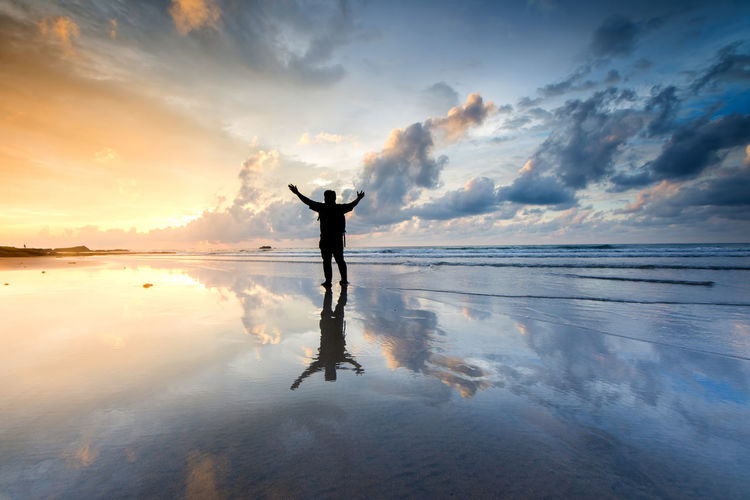 a man standing on wet sand during sunset with reflection. Arms Raised Beauty In Nature Cloud - Sky Horizon Over Water Human Arm Leisure Activity Lifestyles Nature One Person Real People Reflection Scenics - Nature Sea Silhouette Sky Standing Sunset Tranquil Scene Tranquility Water