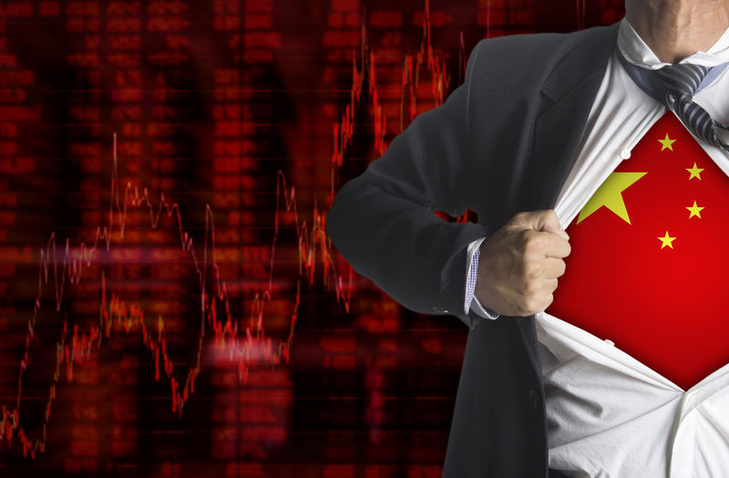 Midsection of businessman showing chinese flag below suit against chart