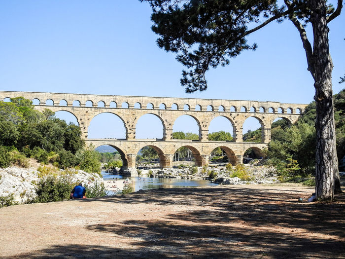 Pont-Du-Gard Arch Architecture Bridge - Man Made Structure Built Structure Clear Sky Day Men Nature One Person Outdoors People Real People Sky Sunlight Tree