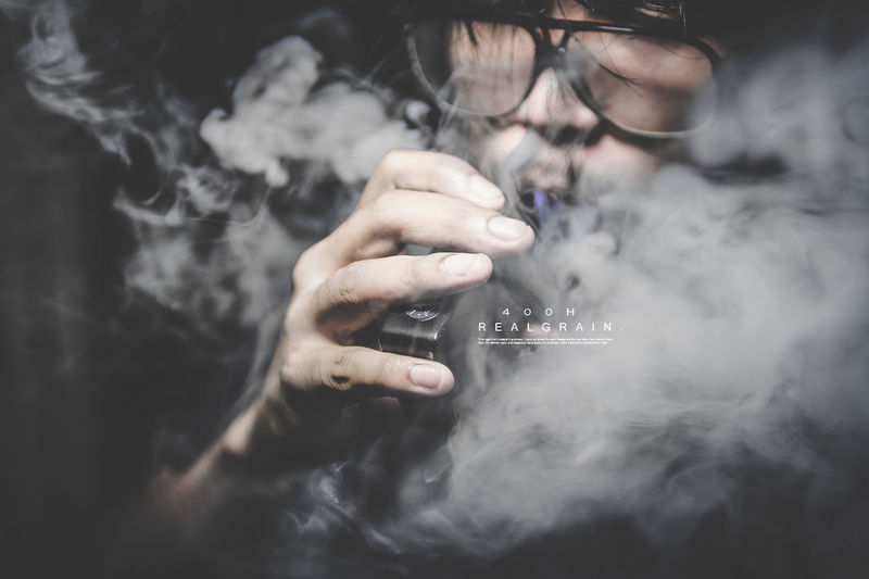 Activity Bad Habit Cigarette  Communication Eyeglasses  Holding Human Body Part Indoors  One Person Real People RISK Sign Smoke - Physical Structure Smoking - Activity Smoking Issues Social Issues Warning Sign