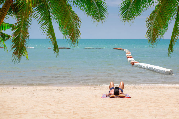 Water Sea Beach Palm Tree Tropical Climate Nature Land Beauty In Nature Leisure Activity Plant Day Tree Sky Real People Sand Lifestyles Scenics - Nature Vacations Horizon Over Water Outdoors Sunbathing Sun Bath Ocean Coconut Palm Tree Relaxing Vacations