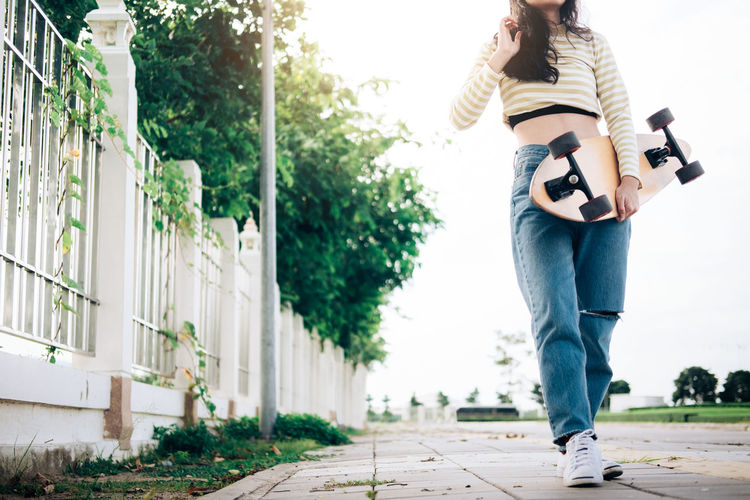 Low section of woman holding skateboard while walking on footpath