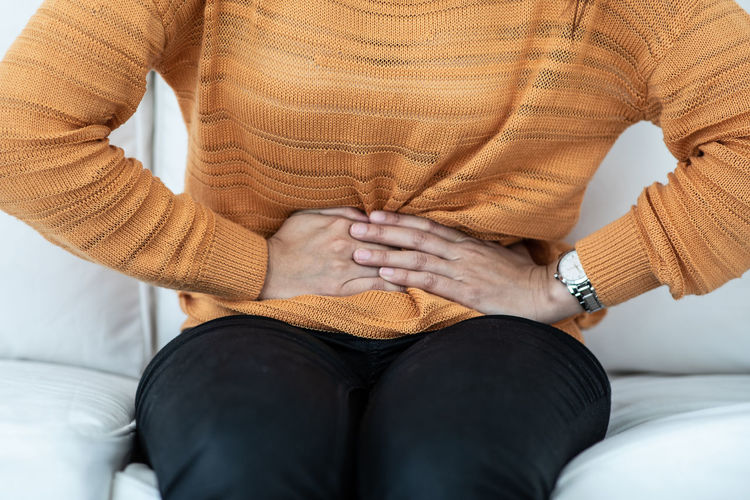 Midsection of woman with stomachache sitting at home