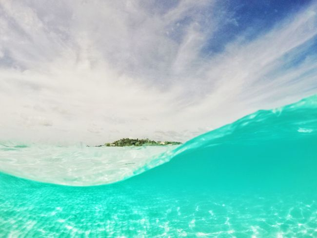 Inbetween Turquoise Colored Tropical Climate Sea Blue Nature Beach Outdoors Water Summer Vacations Beauty In Nature Travel Destinations Horizon Over Water Day Cloud - Sky Scenics Travel No People Sun Sky HalfNHalf Connected By Travel
