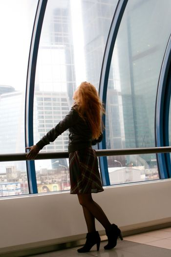 Side view of woman standing by railing in modern building