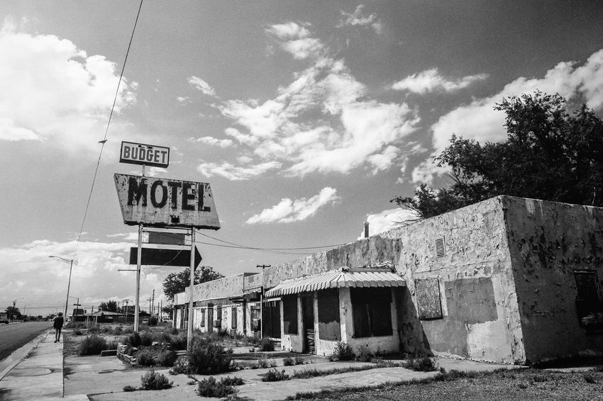 Abandoned Boarded Up Day Falling Apart Motel Motor Lodge Old Building  Outdoors People Road Sign Route 66 Sidewalk Sign Sky And Clouds Yesteryear
