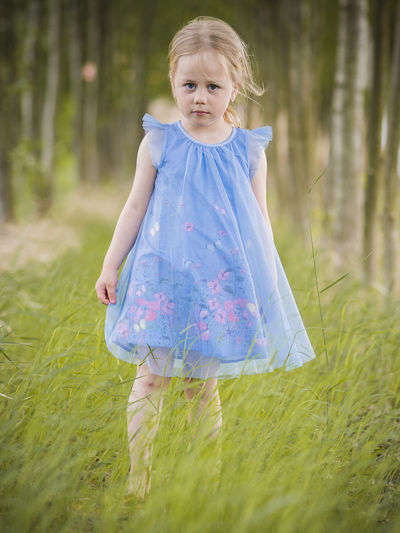 Portrait of cute girl walking on grassy field