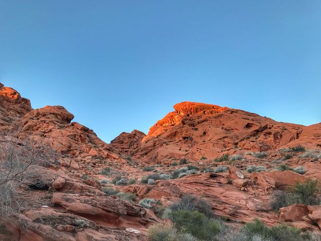 Sunlight hitting the tip of orange sandstone hills Premium Collection Valley Of Fire State Park Tranquil Scene Tranquility Mountain Physical Geography Nature Clear Sky Beauty In Nature Rock - Object Scenics No People Arid Climate Landscape Sky Outdoors Mountain Range Desert Blue Day