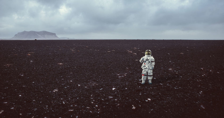 Full length of astronaut standing on field against sky
