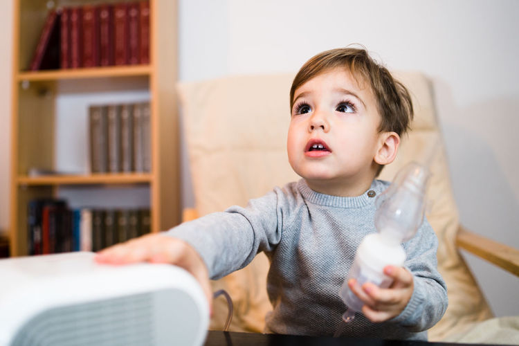 Portrait of cute boy sitting on book at home