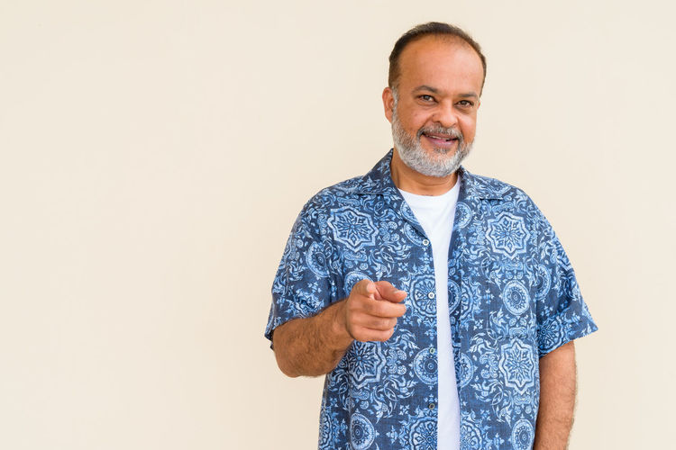 Portrait of smiling man standing against white background