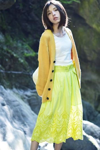 Beautiful young woman standing against yellow outdoors