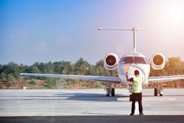 Full length of man standing on airplane against sky
