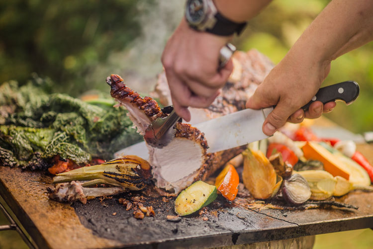Master chef cuts roasted pork on bead of colourful vegetables in sunny green garden