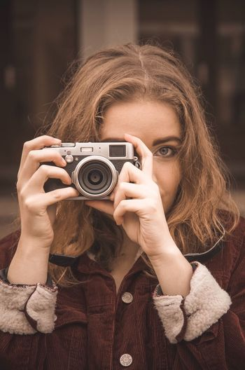 Portrait of woman photographing outdoors