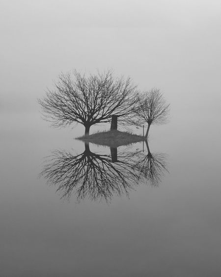 Small island with tree silhouettes and a stone pillar in a lake - Location: Fantasy Beautiful Shades Of Grey Beauty In Nature Black White Black And White Day Foggy Gray Grey Lake Landscape Nature No Colors No People Outdoors Scenics Sky Stone Pillar Tranquil Scene Tranquility Tree Silhouettes Water Without Colors