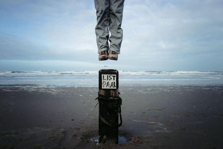 Low Section Of Man Levitating Over Wooden Post At Beach Against Cloudy Sky