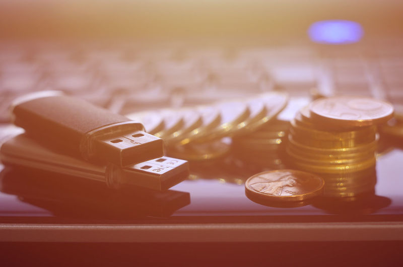 Close-up of coins and usb stick on laptop