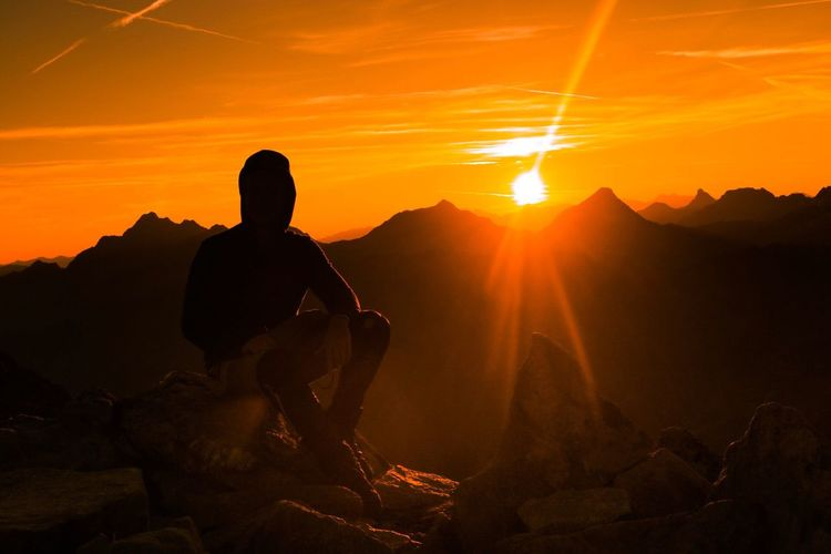 Man Sitting On Mountain Against Sky At Sunset