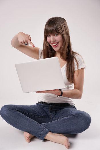 Eine junge Frau, Sabrina, sitzt auf dem Boden, auf ihrem Schoß hat sie einen Laptop / Notebook Barefeet Barfuß Computer Electronic Fingernägel Freude Fussel Fuß Fußnägel Füsse Girl Jeans Junge Frau Lachend Lange Haare Laptop Long Hair Mädchen Notebook Rote Nägel Shirt Software Tshirt White Shirt Young Women