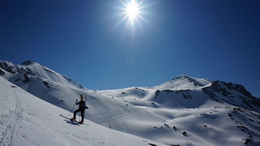 Man skiing on snowcapped mountain against clear sky