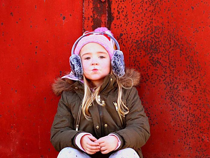 Portrait of girl puckering while sitting against metallic wall