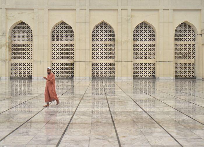 Full length of man walking on floor against building