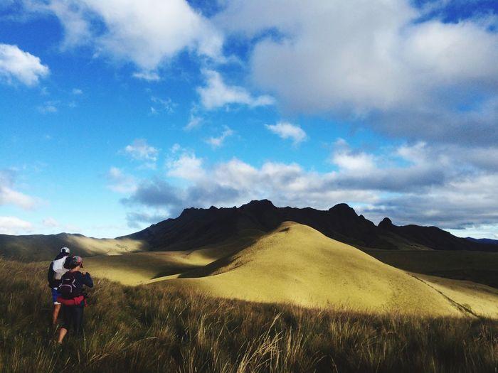 Rear View Of Friends Walking On Landscape Against Cloudy Sky