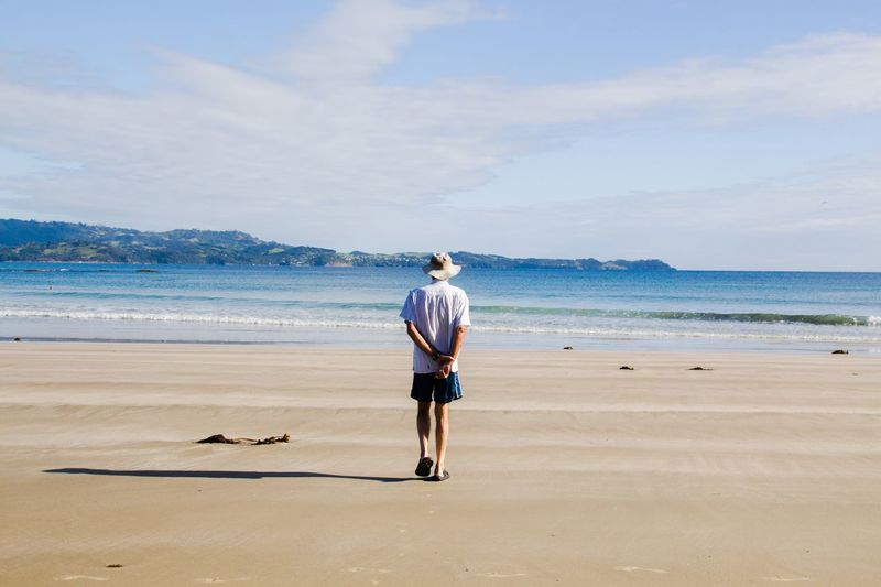 Rear View Of Man Walking At Beach Against Sky During Sunny Day