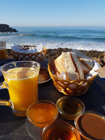 Close-up of breakfast served on table against sea