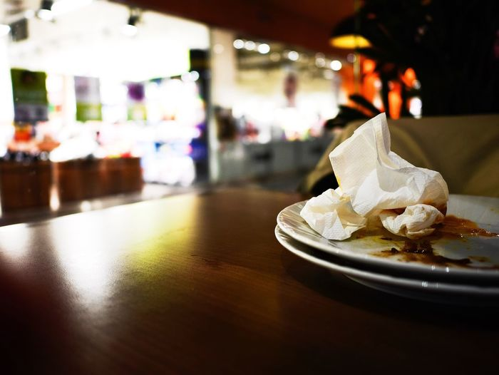 Close-up of messy plates on table at restaurant