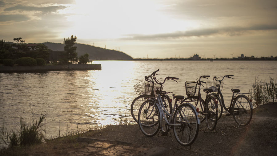 Water Sky Bicycle Transportation Nature Cloud - Sky Sunset Mode Of Transportation Land Vehicle River Plant No People Stationary Tranquil Scene Tranquility Outdoors Beauty In Nature Tree