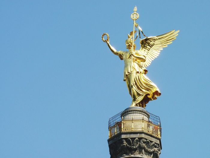 Low angle view of gold statue on berlin victory column against clear sky
