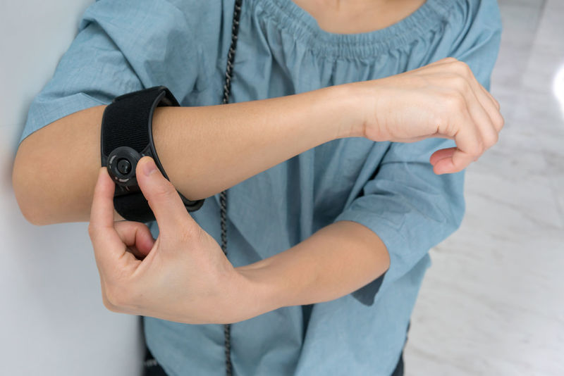 Asian woman wearing black elbow brace with adjustable button to reduce pain on white background Adult Asian  Bones Healthcare Woman Ache Body Part Discomfort Female Healthy Hurt Inflamation Injury Medical Muscle Painful Physical Reduce Tennis Elbow