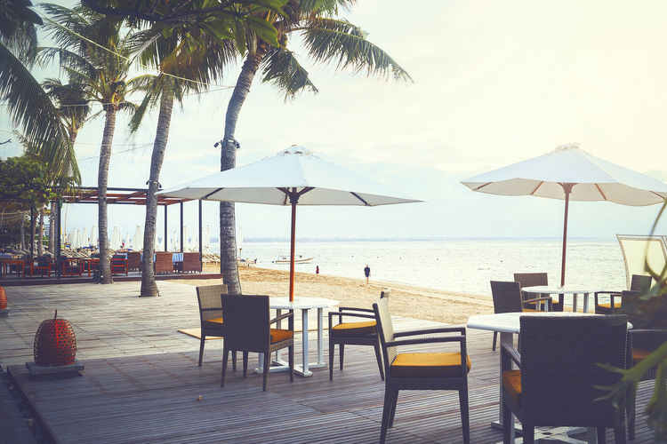 Cafe and restaurant chairs with table and umbrella at beach. Famous travel destination in Sanur, Bali, Indonesia. Bali, Indonesia INDONESIA Beach Beauty In Nature Chair Day Horizon Over Water Idyllic Luxury Nature No People Outdoors Relaxation Restaurant Sand Sanur Beach Scenics Sea Sky Table Tourist Resort Tranquil Scene Tranquility Travel Destinations Vacations