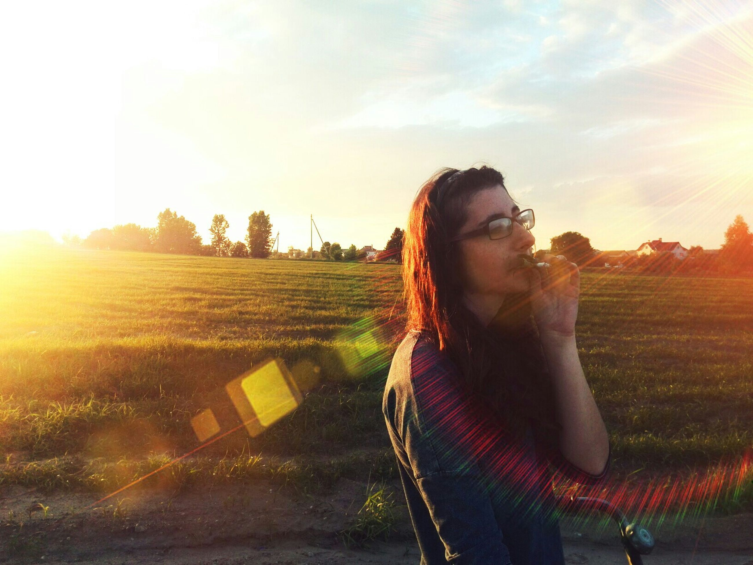 young adult, person, young women, lifestyles, leisure activity, sun, sunbeam, sunlight, sky, field, long hair, casual clothing, sunset, lens flare, portrait, looking at camera, sunglasses, grass
