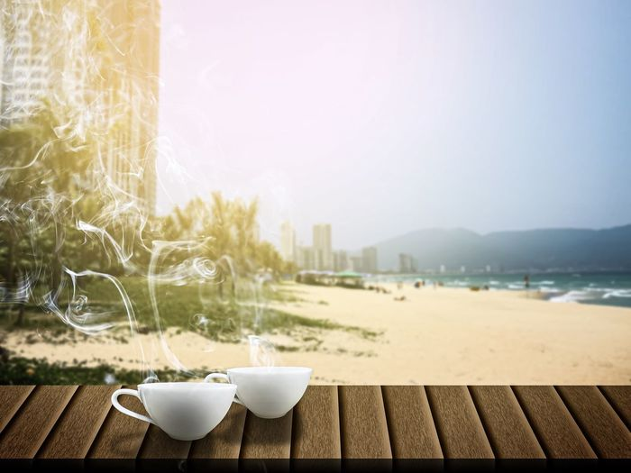 Coffee cup on table by sea against sky