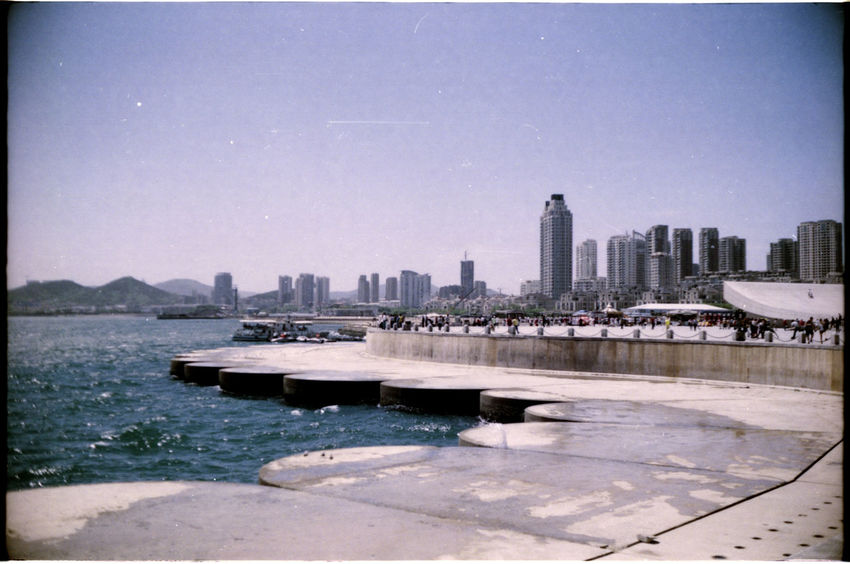 Analogue Photography Architecture Blue Sky Built Structure China City Cityscape Clear Sky Day Group Of People Outdoors S Skyline Skyscraper Summer Urban Skyline Water Waterfront Xinghai Square