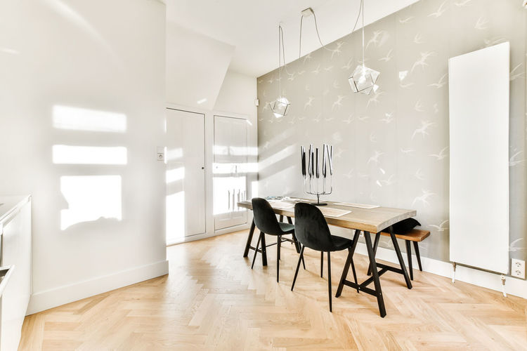 Empty chairs and table against white wall