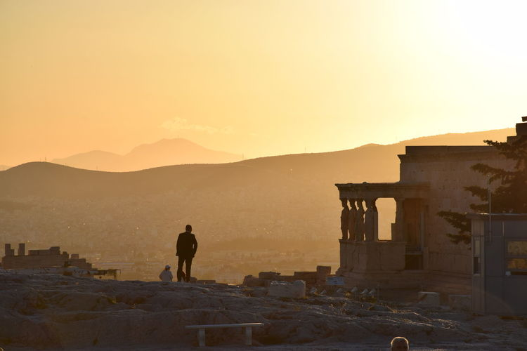 Rear view of man standing by historic building by mountains against clear sky during sunset
