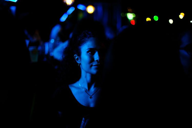 Young woman looking away while standing against illuminated lights at night